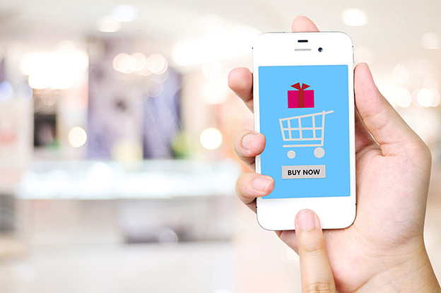 Hand holding smart phone over blur store background, e-commerce, business and technology concept