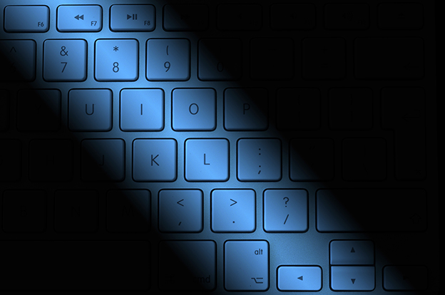 Computer keyboard overlaid with blue lighting and shadows